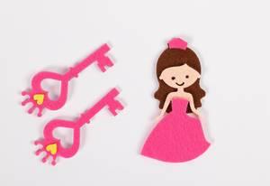 Zwei pinke Schlüssel und Figur einer Prinzessin aus Papier mit rosarotem Kleid vor weißem Hintergrund