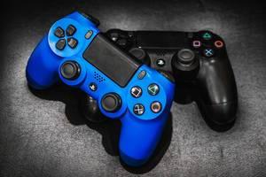 Zwei Playstation-Controller in blau und schwarz unter Scheinwerferlicht auf dunklem Untergrund