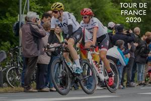 """Zwei Radrennfahrer auf ihren Rennrädern, mit Zuschauern am Straßenrand, neben der Aufschrift """"Tour de France 2020"""""""