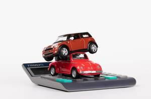 Zwei rote Spielzeugautos auf einem Taschenrechner