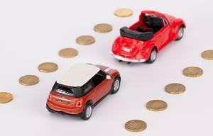 Zwei rote Spielzeugautos fahren auf einer 20-Cent-Münzen-Straße