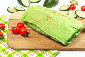 Zwei Schawarma Wraps in grünem Pitabrot auf einem Holzbrett mit Tomaten und Gurken