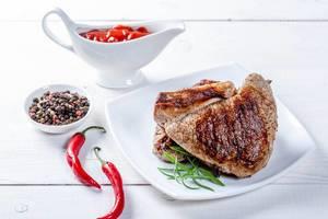 Zwei schmackhafte Rindersteaks mit Chilis, Pfefferkörnern und Soße auf weißem Holztisch