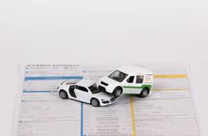 Zwei Spielzeugautos auf einer noch nicht vervollständigten Unfallschadenmeldung