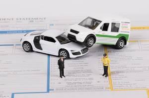 Zwei Spielzeugautos in einem Autounfall auf Versicherungsunterlagen