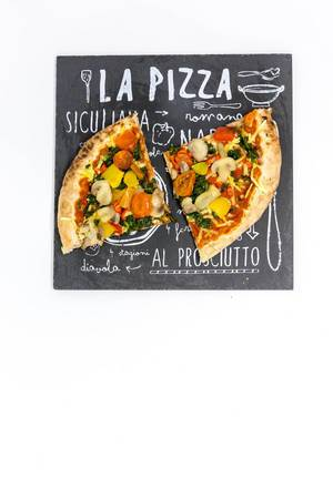 Zwei Stücke Gemüsepizza auf einem Pizzeriaschild - mit Tomaten, Pilzen, Spinat und gelber Paprika
