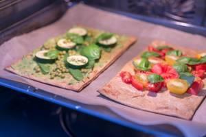 Zwei vegane Pizzen mit frischen Zutaten belegt im Ofen