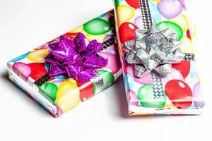 Zwei verpackte Geburtstagsgeschenke auf einem weißem Tisch
