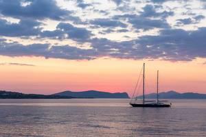Zweimaster-Segelboot auf dem Meer, mit Sonnenuntergang und rötlichem Himmel im Hintergrund